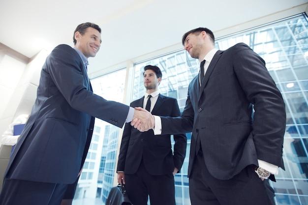 Empresários apertando as mãos, terminando uma reunião no escritório