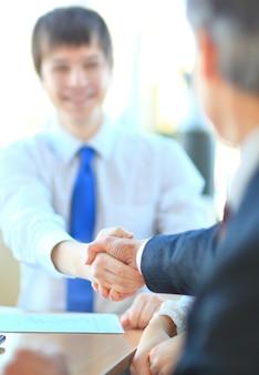 Empresários apertando as mãos, terminando uma reunião
