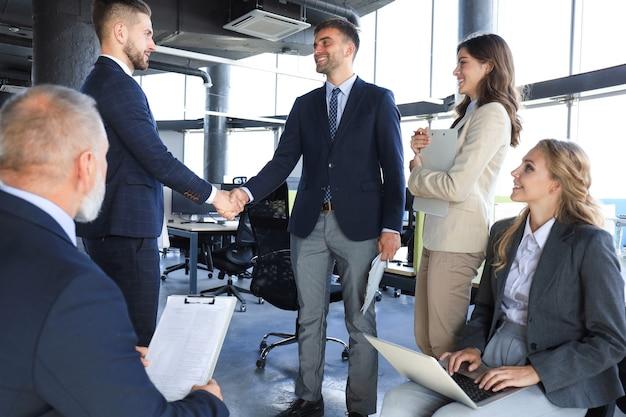 Empresários apertando as mãos, terminando uma reunião.