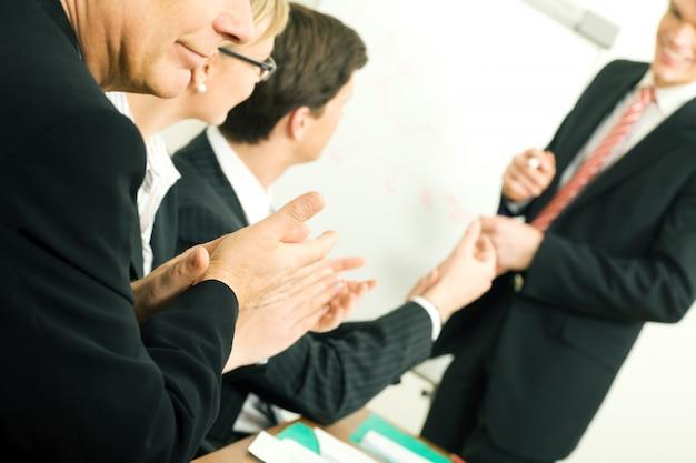 Empresários aplaudindo em uma reunião