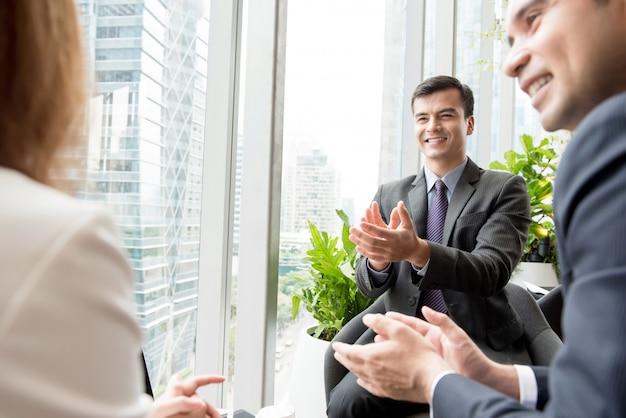 Empresários, aplaudindo seus colegas no salão do prédio de escritórios