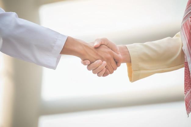 Empresários árabes apertam as mãos e aceitam negócios para o trabalho em equipe.