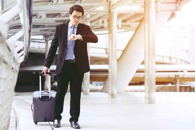 Empresários arrastam bagagens em direção ao aeroporto.
