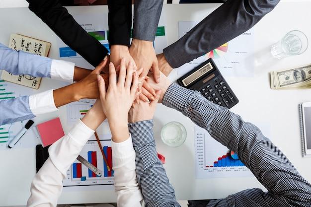Empresários as mãos na mesa branca com documentos e rascunhos