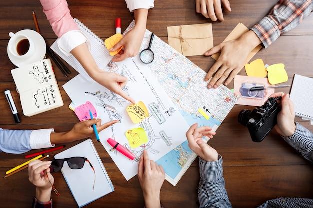 Empresários as mãos na mesa de madeira com documentos e rascunhos