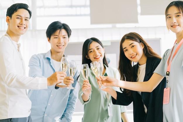 Empresários asiáticos brindam com seus copos comemorando os resultados