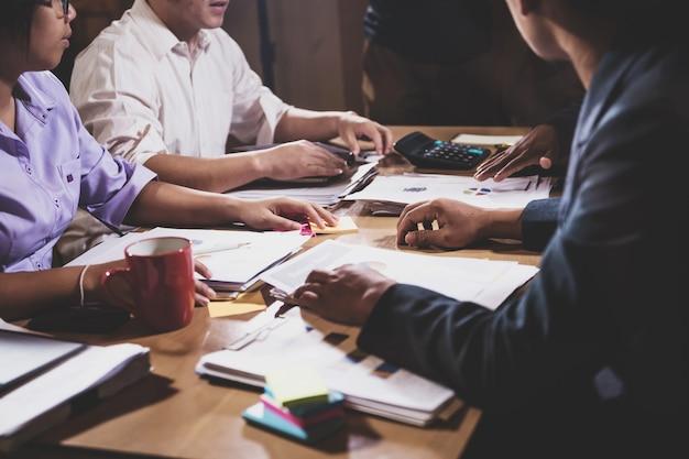 Empresários asiáticos, discutindo o trabalho sentado na sala de conferências do escritório na cena noturna