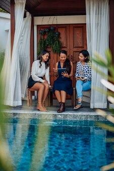 Empresários asiáticos do sexo feminino trabalham juntos usando um tablet sentado em um banco ao redor da piscina em uma villa.