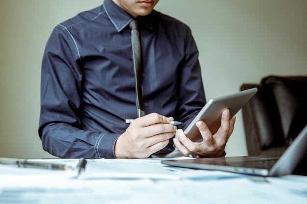 Empresários asiáticos estão usando comprimidos e canetas para analisar a economia.