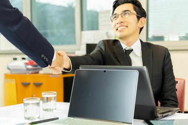 Empresários bem sucedidos handshak acordo após bom negócio em off