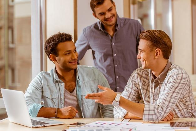 Empresários bonitos em roupas sorrindo e discutindo.