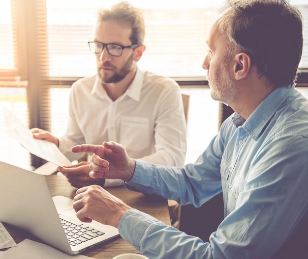 Empresários bonitos estão usando um laptop.
