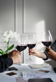 Empresários brindando vinho tinto no escritório