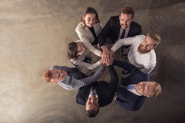 Empresários colocando as mãos juntos no conceito de integração, trabalho em equipe e parceria