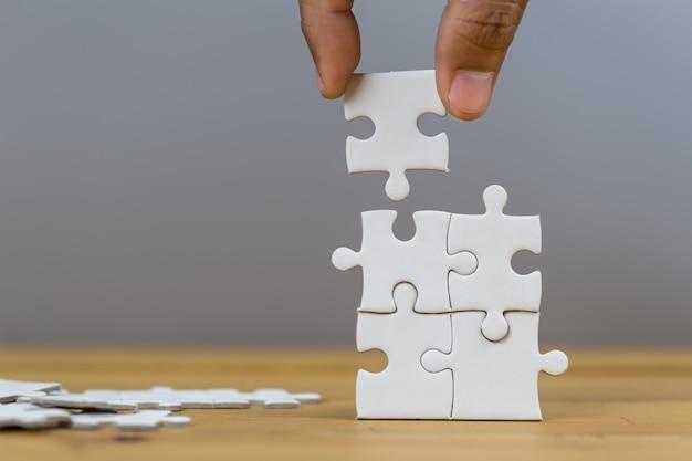 Empresários colocar a última peça de quebra-cabeça, conceito de serviço de negócios para o sucesso.