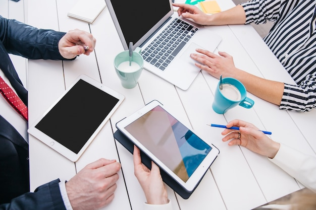 Empresários com dispositivos na mesa