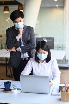Empresários com máscara protetora, analisando cifras financeiras, denotando o progresso com o laptop no escritório moderno.