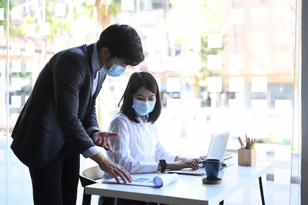 Empresários com máscara protetora são especialistas financeiros que discutem informações durante o processo de contabilidade no escritório.