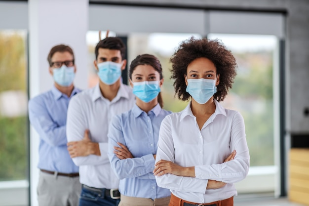 Empresários com máscaras em pé com os braços cruzados.