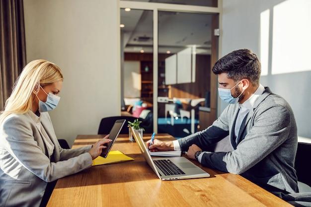 Empresários com máscaras se sentam em uma mesa no escritório e fazem seu trabalho