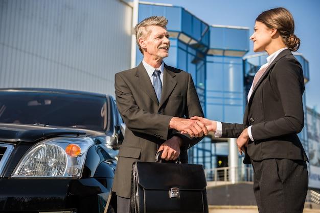 Empresários confiantes em ternos apertando as mãos.