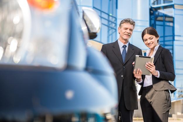 Empresários confiantes em trajes usando tablet perto de carro.