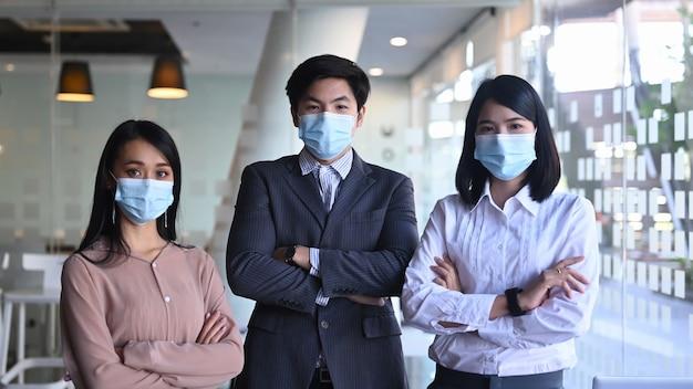 Empresários confiantes usando máscara médica em pé com os braços cruzados em um escritório moderno.