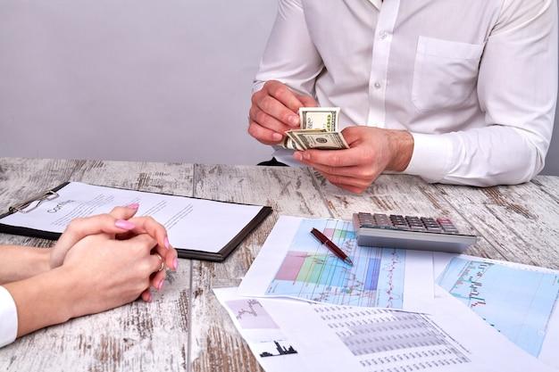 Empresários contando dinheiro depois de fechar um acordo
