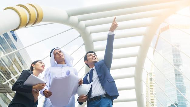 Empresários conversam e apresentam ao homem árabe o planejamento de uma cidade ao ar livre