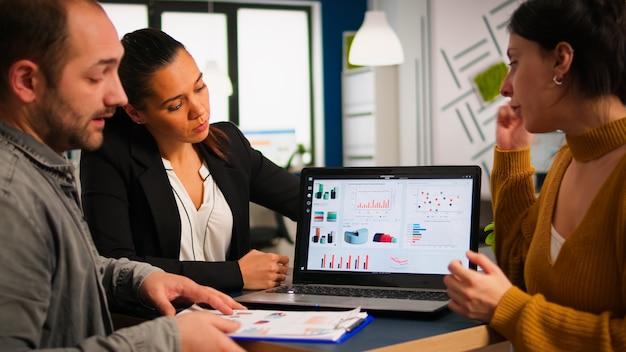 Empresários conversando com o líder da equipe usando a prancheta com documentos apontando nela, apresentando ideias financeiras de inicialização ao gerente, brainstorming da estratégia de gerenciamento de projetos no escritório da empresa