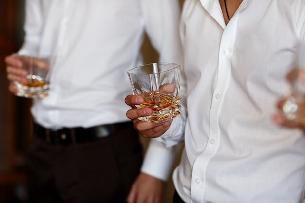 Empresários de amigos elegantes de terno brindando com copos de uísque dentro de casa, closeup. manhã do noivo