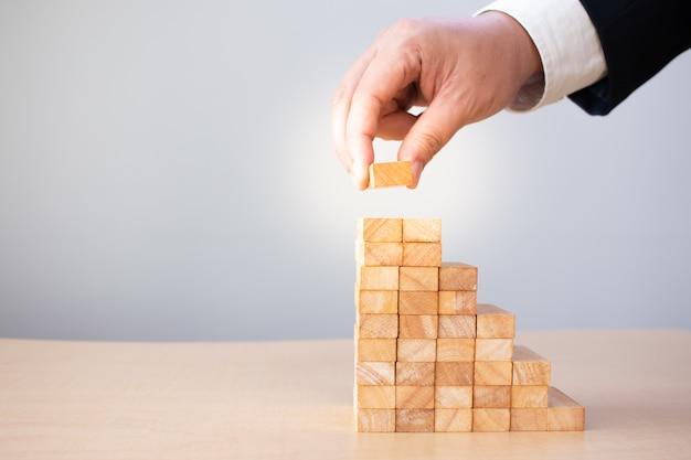 Empresários de blocos de madeira à mão empilhados para desenvolver uma etapa da escada, gerenciamento de riscos, para o crescimento do sucesso planejado.