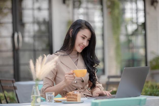 Empresários de designers tailandeses sentado bebendo café e bolo, mantendo o trabalho no laptop via internet wi-fi
