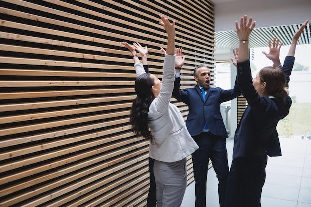 Empresários de pé com as mãos levantadas