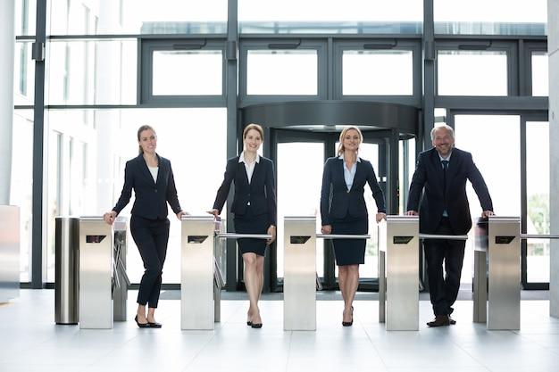 Empresários de pé no portão da catraca