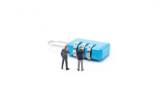 Empresários de pessoas em miniatura analisam a senha da chave azul