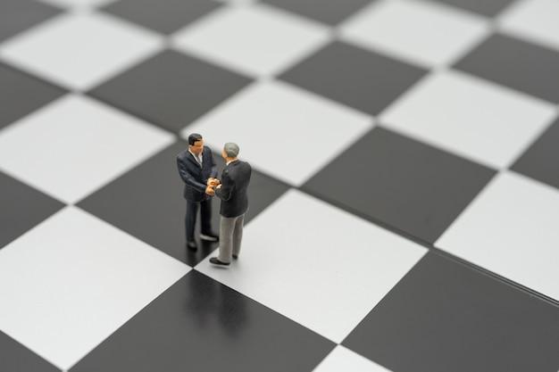 Empresários de pessoas em miniatura apertem as mãos em pé em um tabuleiro de xadrez com um xadrez