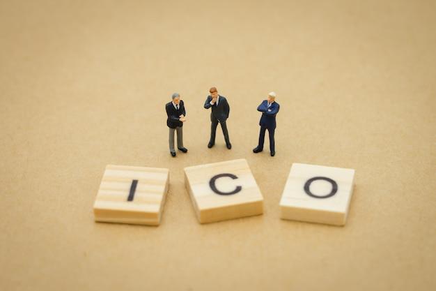 Empresários de pessoas em miniatura de pé com palavra de madeira ico (oferta de moeda inicial)