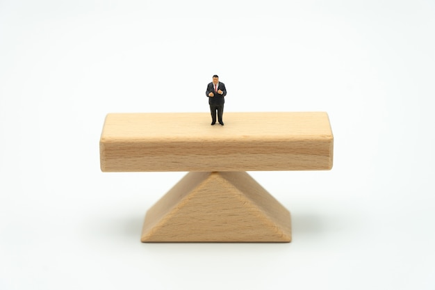 Empresários de pessoas em miniatura de pé em vigas de madeira permanente em ambos os lados