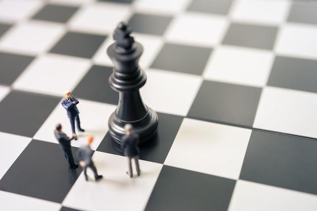 Empresários de pessoas em miniatura, de pé sobre um tabuleiro de xadrez com uma peça de xadrez na