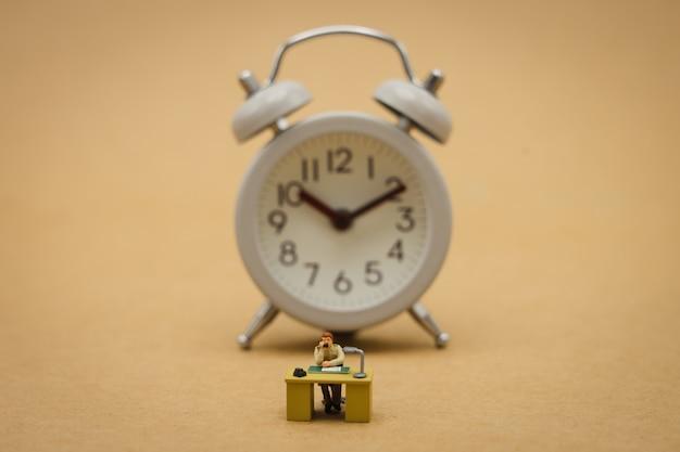 Empresários de pessoas em miniatura e relógio vintage sentado horas extras