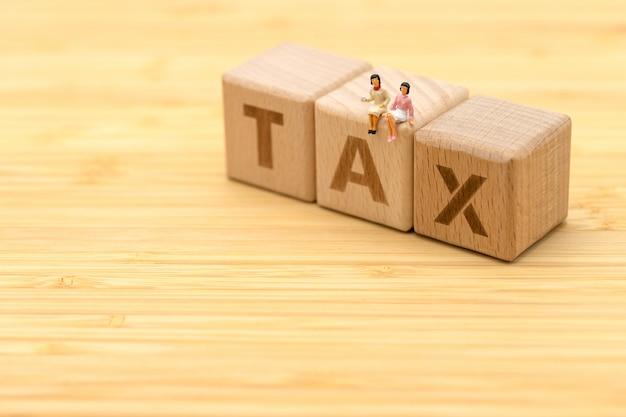 Empresários de pessoas em miniatura em pé com madeira palavra imposto usando como pano de fundo