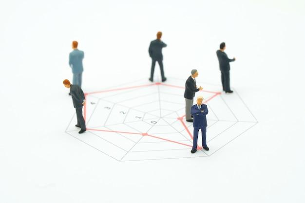 Empresários de pessoas em miniatura em pé em um círculo gráficos de várias habilidades