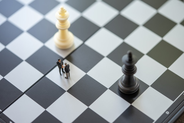 Empresários de pessoas em miniatura em pé em um tabuleiro de xadrez com uma peça de xadrez