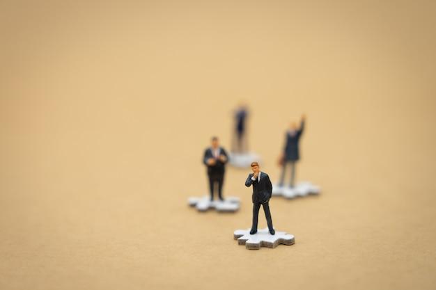 Empresários de pessoas em miniatura em pé na serra de vaivém branco