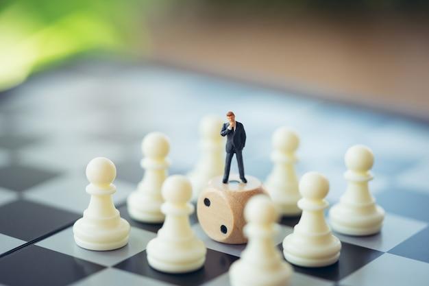 Empresários de pessoas em miniatura permanente análise de xadrez comunicar