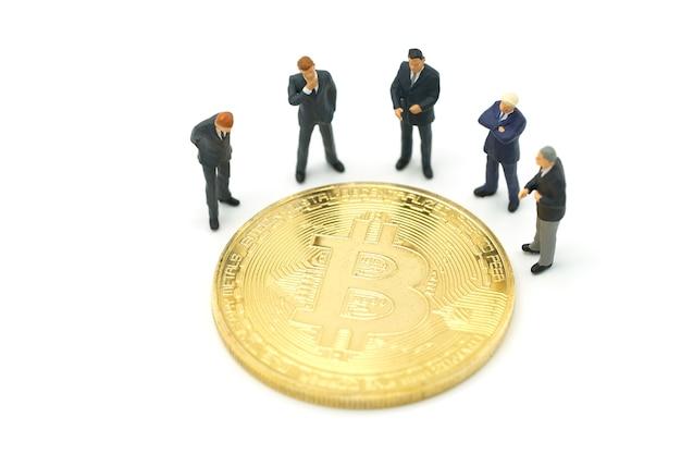 Empresários de pessoas em miniatura permanente moeda de bit de ouro de análise de investimento