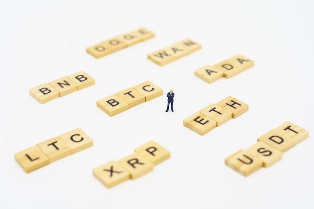 Empresários de pessoas em miniatura que estão o símbolo da criptomoeda de análise de investimento. comunicações para investir no mercado digital. usando como conceito de negócio de plano de fundo com espaço de cópia.