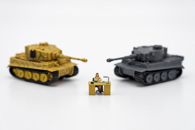 Empresários de pessoas em miniatura, sentado em um tabuleiro de xadrez com um modelo de tanque