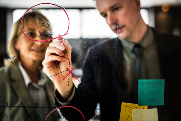 Empresários de planejamento em uma parede de vidro